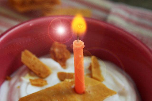 orange candle lit in brittle holder flare