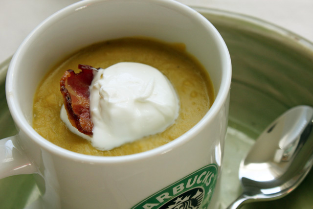 split green pea soup in a mug with bacon garnish