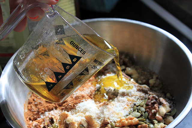 pour olive oil in granola miz bowl
