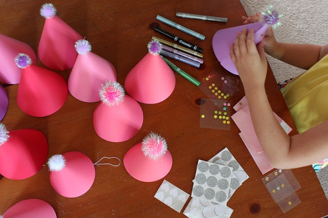 a decorating paper party hats pom poms